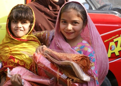 Pakistani girls carrying supplies